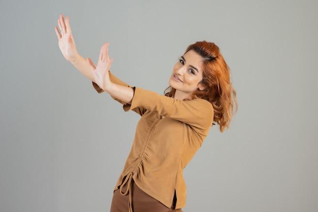 Uśmiechnięta ruda trzymając ręce w górę i patrząc na kamery na szaro.