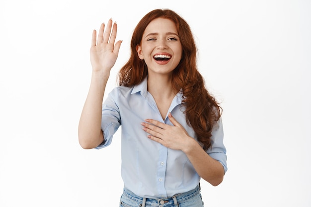 Uśmiechnięta ruda z podniesioną ręką na białym