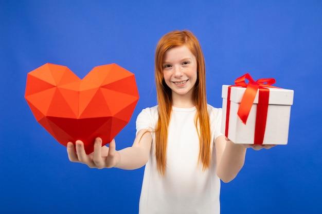 Uśmiechnięta rudowłosa dziewczyna wyciąga pudełko i czerwone serce niebieskie