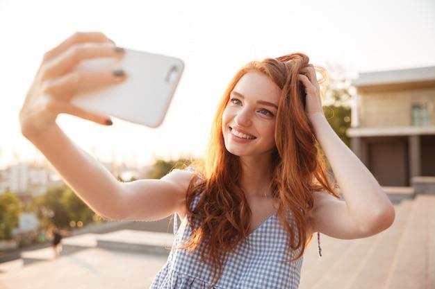 Uśmiechnięta rudzielec kobieta z długie włosy bierze selfie