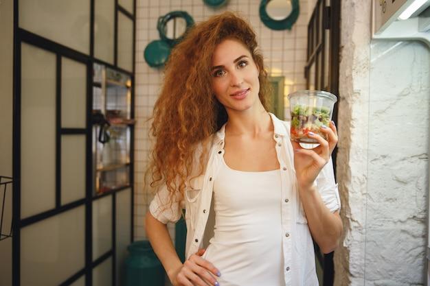 Uśmiechnięta rudzielec młodej damy pozycja w kawiarni podczas gdy trzymający sałatki.