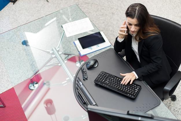 Uśmiechnięta sekretarka rozmawia przez telefon podczas pracy z komputerem, widziana z góry