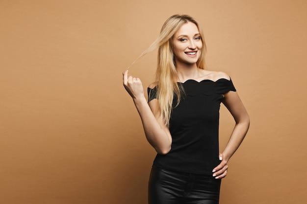 Uśmiechnięta, seksowna i piękna blondynka modelka o idealnym ciele w czarnych skórzanych spodniach i czarnej koszulce regulującej włosy, uśmiechająca się i pozuje przy pomarańczowej ścianie