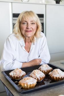 Uśmiechnięta seniorwoman opiera na stole z tacą do pieczenia