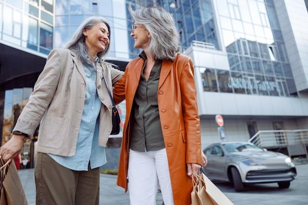 Uśmiechnięta siwowłosa azjatycka kobieta przytula dojrzałą damę trzymającą torby na zakupy na ulicy miasta