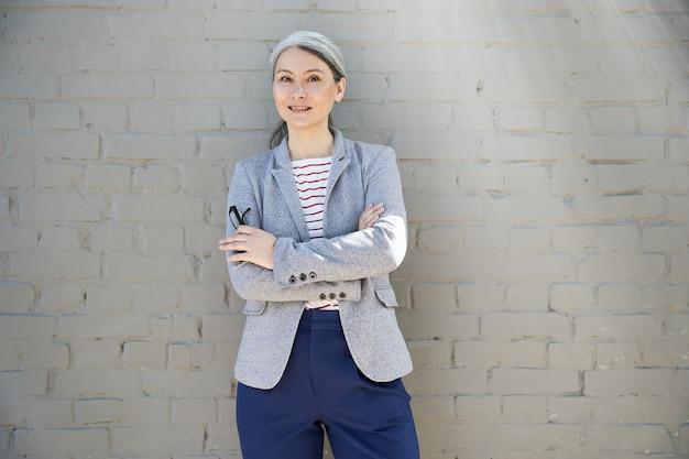 Uśmiechnięta siwowłosa dama w eleganckim stroju stojąca przy ścianie ze skrzyżowanymi rękami arms
