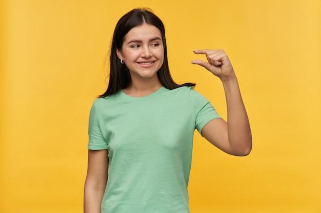 Uśmiechnięta śliczna brunetka młoda kobieta w miętowej koszulce stojąca i pokazująca mały rozmiar palcami odizolowanymi na żółtej ścianie