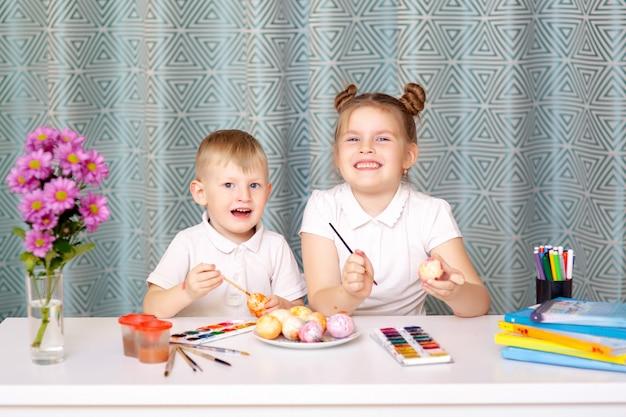 Uśmiechnięta śliczna dziewczyna i jej młodszy brat maluje jeden jajka podczas gdy oba przygotowywający na wielkanocnego wakacje