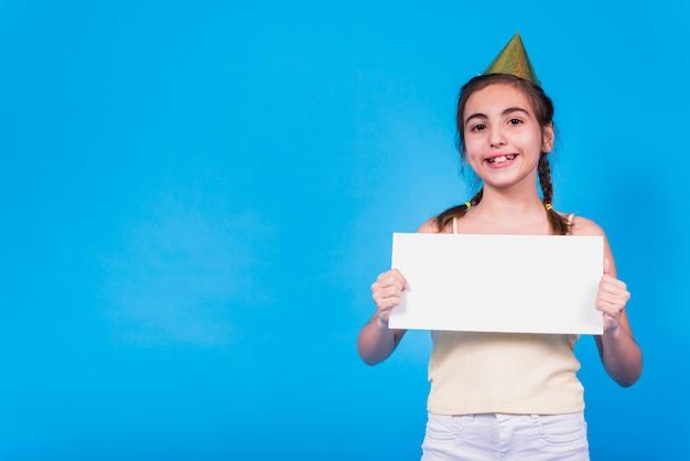 Uśmiechnięta śliczna dziewczyna jest ubranym partyjnego kapelusz trzyma pustą kartę w ręce przed barwioną tapetą