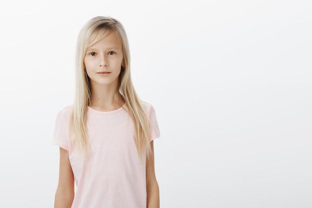 Uśmiechnięta śliczna dziewczyna patrząc na kamery na białym tle
