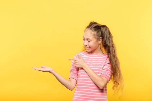 Uśmiechnięta śliczna dziewczyna patrząc na wirtualny obiekt w rękach i wskazując na to. puste miejsce na reklamę lub lokowanie produktu.