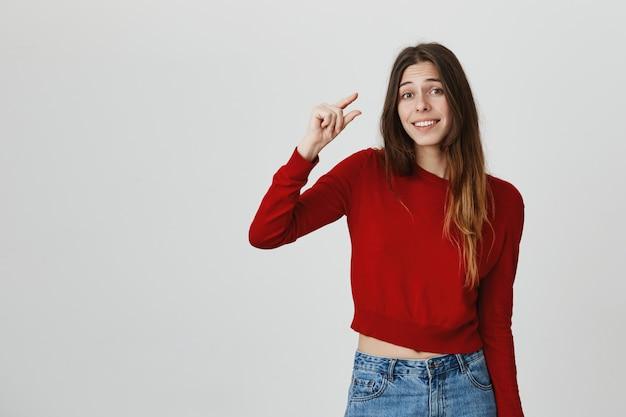 Uśmiechnięta śliczna dziewczyna pokazuje coś małego, malutkiego lub małego z gestem ręki