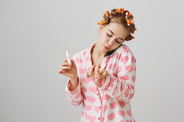 Uśmiechnięta śliczna dziewczyna rozmawia przez telefon i polski paznokcie w lokówki i piżamy