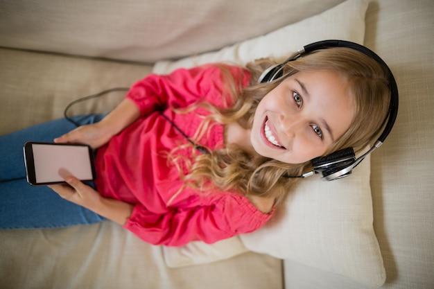 Uśmiechnięta śliczna dziewczyna słucha muzyka na hełmofonach w żywym pokoju w domu
