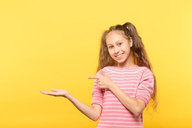 Uśmiechnięta śliczna dziewczyna trzyma w rękach wirtualny obiekt i wskazuje na niego