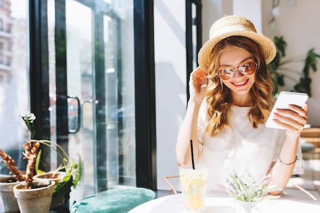 Uśmiechnięta śliczna dziewczyna w słomkowym kapeluszu relaks w kawiarni obok szklanych drzwi trzymając w ręku smartfon
