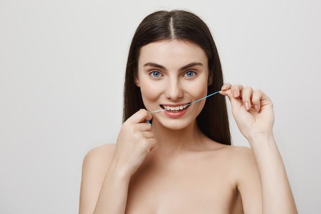 Uśmiechnięta śliczna kobieta czyści zęby nicią dentystyczną