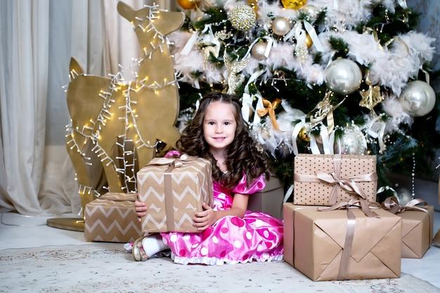Uśmiechnięta śliczna mała dziewczynka blisko pobliskich prezentów i choinki.