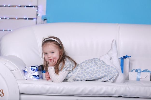 Uśmiechnięta śliczna mała dziewczynka leży na białej kanapie. duży biały zegar i misia na ścianie. obchody nowego roku i bożego narodzenia.