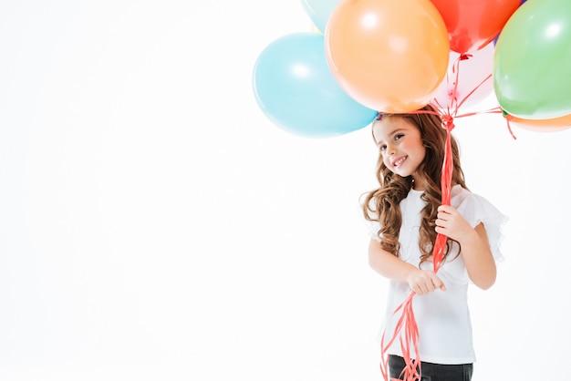 Uśmiechnięta śliczna mała dziewczynka stoi kolorowych balony i trzyma