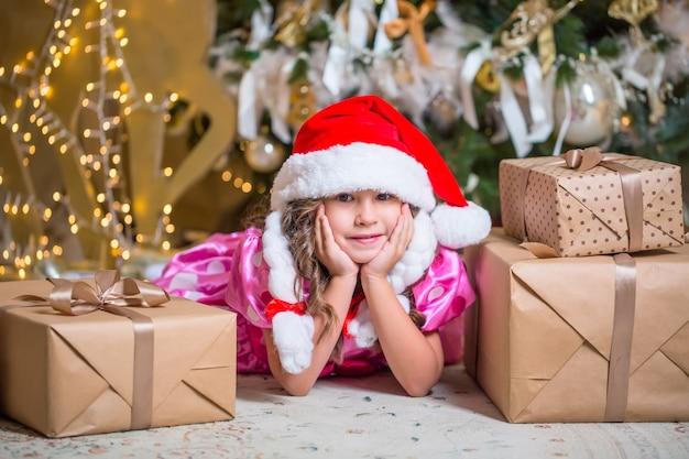 Uśmiechnięta śliczna mała dziewczynka w pobliżu prezentów i choinki.