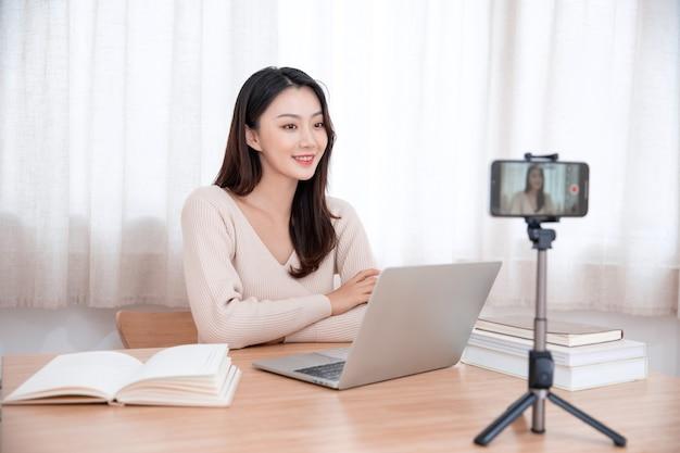 Uśmiechnięta śliczna młoda azjatykcia kobieta blogger nagrywanie wideo