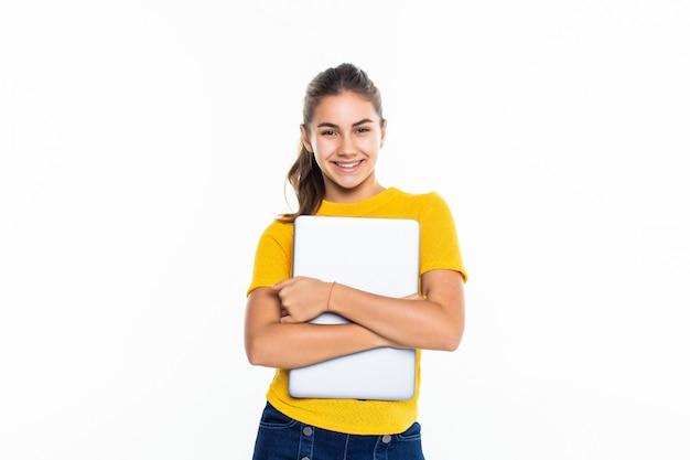 Uśmiechnięta śliczna nastoletnia dziewczyna używa laptop nad biel ścianą