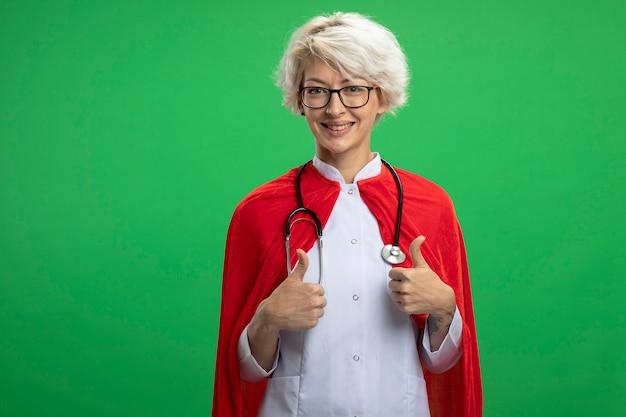 Uśmiechnięta słowiańska kobieta superbohatera w mundurze lekarza z czerwoną peleryną i stetoskopem w okularach optycznych kciuki w górę dwóch rąk odizolowanych na zielonej ścianie z miejscem na kopię