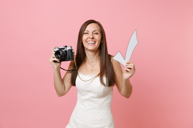 Uśmiechnięta śmieszna kobieta w białej sukni, trzymająca retro vintage aparat fotograficzny i znacznik wyboru, wybierająca personel, fotograf
