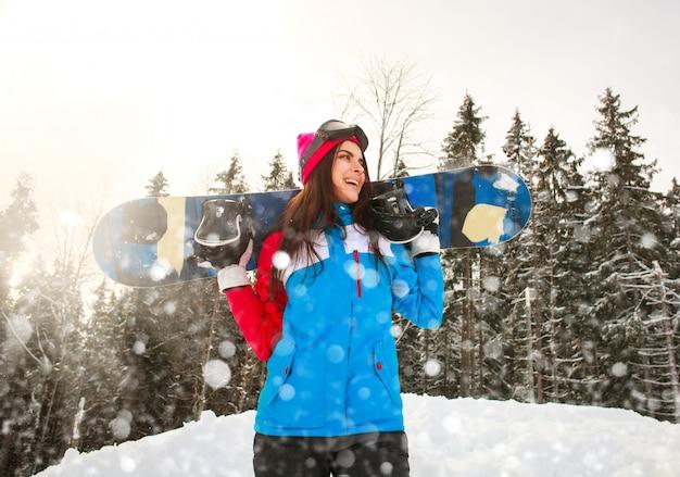 Uśmiechnięta snowboarder dziewczyna w zimie w opadzie śniegu na sosnowym lesie