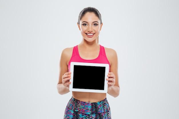 Uśmiechnięta sportowa kobieta pokazująca pusty ekran komputera typu tablet