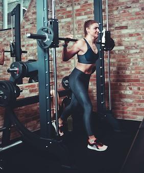 Uśmiechnięta Sportowa Kobieta Robi Rzuca Się Z Smith Maszyną. Premium Zdjęcia
