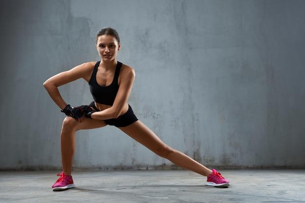 Uśmiechnięta sportsmenka ćwiczy wypady na bok