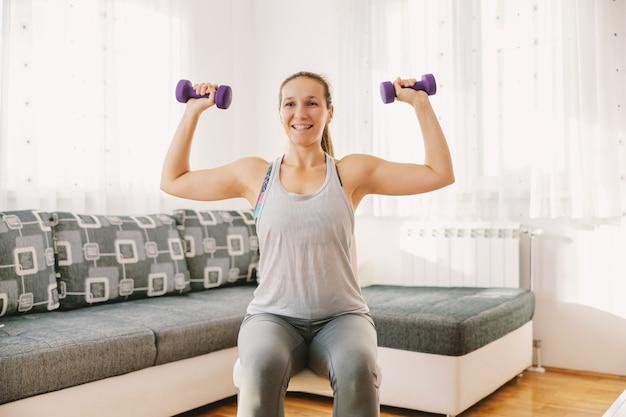 Uśmiechnięta sportsmenka siedzi na krześle w swoim mieszkaniu i robi ćwiczenia na biceps. jeśli nie możesz chodzić na siłownię, możesz zrobić własną w domu.