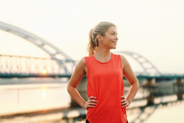 Uśmiechnięta sporty blondynki kobieta z kucyka stać plenerowy z rękami na biodrach. koncepcja fitness na świeżym powietrzu.