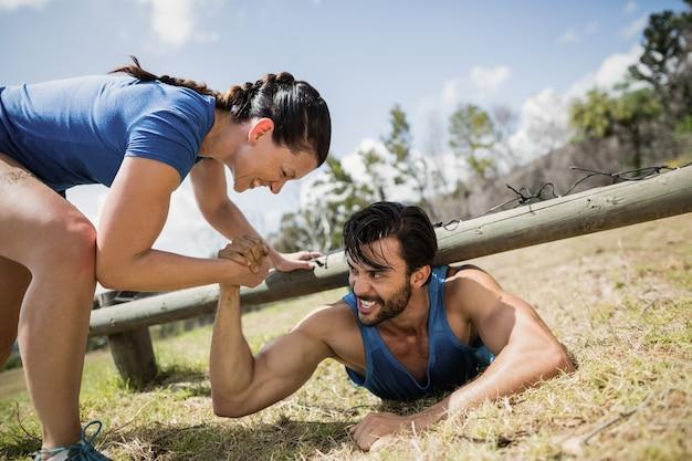 Uśmiechnięta sprawna kobieta pomaga człowiekowi czołgać się pod siatką podczas toru przeszkód w obozie