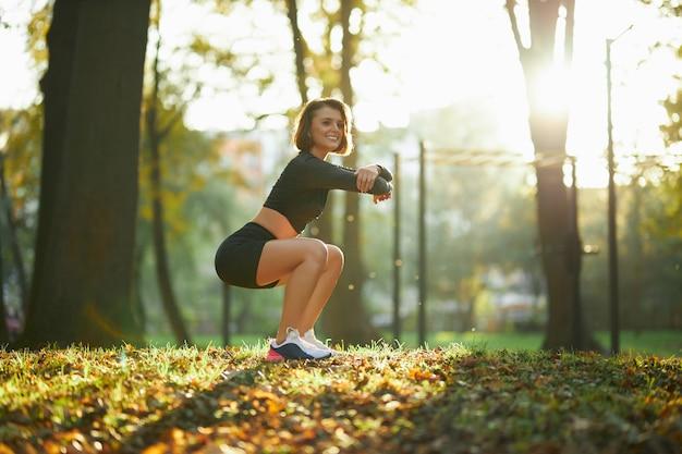 Uśmiechnięta sprawna kobieta robi ćwiczenia fitness w parku