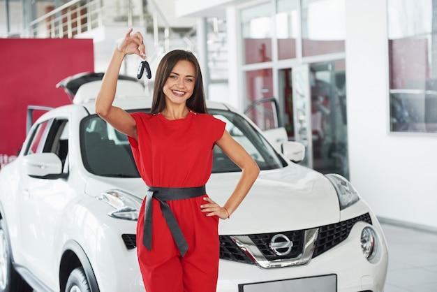 Uśmiechnięta sprzedawczyni samochodów przekazuje twój nowy kluczyki, przedstawicielstwo handlowe i pojęcie sprzedaży.