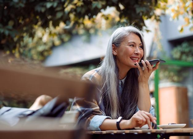 Uśmiechnięta srebrnowłosa azjatka używa trybu głośnika na smartfonie na tarasie kawiarni na świeżym powietrzu