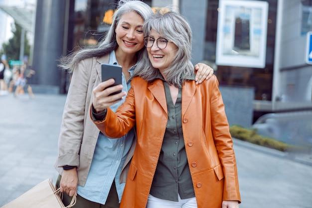 Uśmiechnięta srebrnowłosa dama i towarzyszka z torbami na zakupy robią sobie selfie na nowoczesnej ulicy miasta