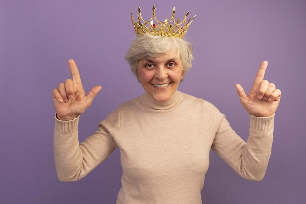 Uśmiechnięta stara kobieta ubrana w kremowy sweter z golfem i koronę skierowaną do góry