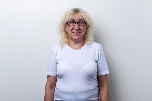 Uśmiechnięta stara kobieta w białej koszulce z okularami na jasnym tle.