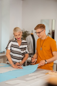 Uśmiechnięta starsza atrakcyjna kobieta naciskająca papierowy wzór, podczas gdy jej młody kolega