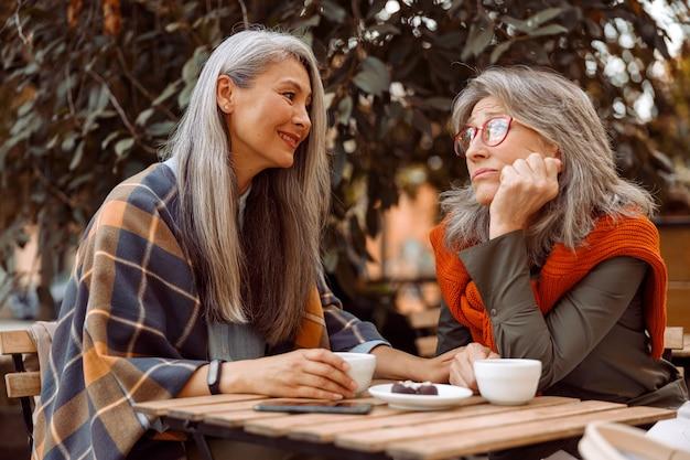 Uśmiechnięta starsza azjatycka kobieta trzyma rękę zdenerwowanego przyjaciela siedzącego razem w ulicznej kawiarni