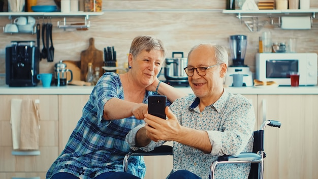 Uśmiechnięta starsza kobieta i jej mąż niepełnosprawny na wózku inwalidzkim za pomocą smartfona w kuchni. sparaliżowany niepełnosprawny staruszek przy użyciu nowoczesnych technologii komunikacyjnych.