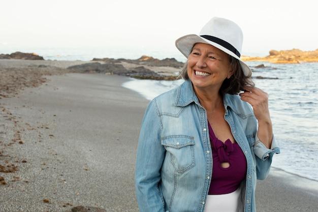 Uśmiechnięta starsza kobieta na plaży, ciesząc się swoim dniem