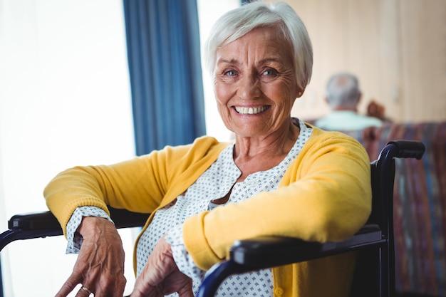 Uśmiechnięta starsza kobieta na wózku inwalidzkim