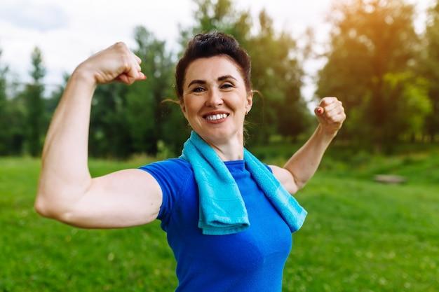 Uśmiechnięta starsza kobieta napina mięśnie plenerowych w parku. starsza kobieta pokazuje biceps