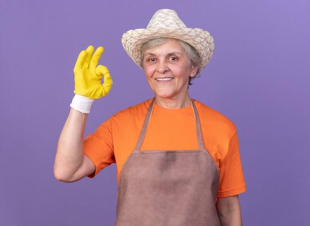 Uśmiechnięta starsza kobieta ogrodniczka w kapeluszu ogrodniczym i rękawiczkach, gestykulująca ok śpiewać odizolowana na fioletowej ścianie z miejscem na kopię