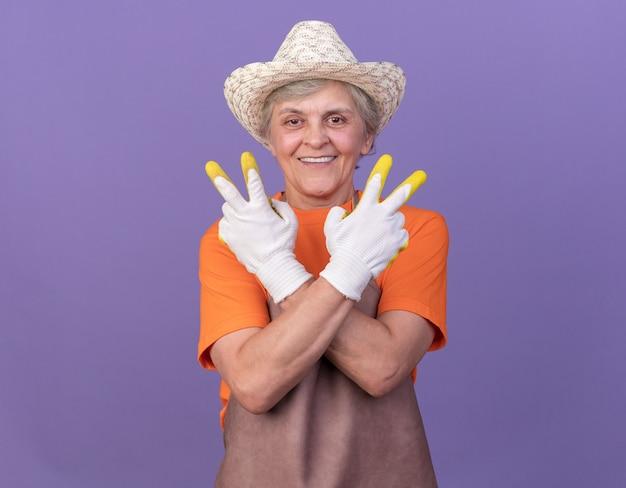 Uśmiechnięta starsza kobieta ogrodniczka w kapeluszu ogrodniczym i rękawiczkach, krzyżująca ręce, gestykulująca znak zwycięstwa